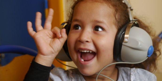 niña con audífonos y su emotiva reacción al escuchar